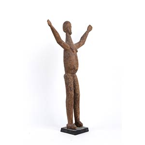 A WOOD SCULPTURE OF A FIGURE WITH RAISED ...
